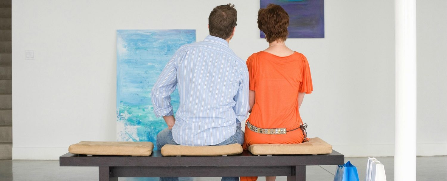Couple admiring a painting at one of the best Greenwich art galleries