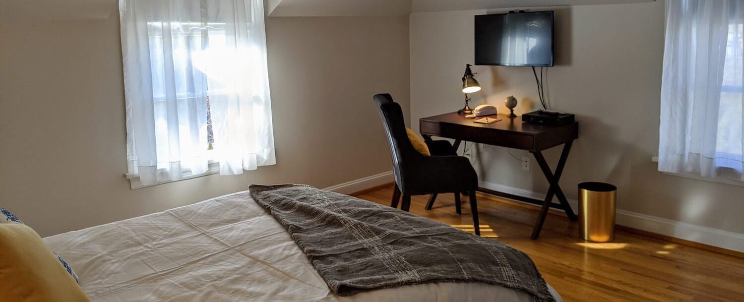 view of the desk, TV, bed, and windows in Room 32