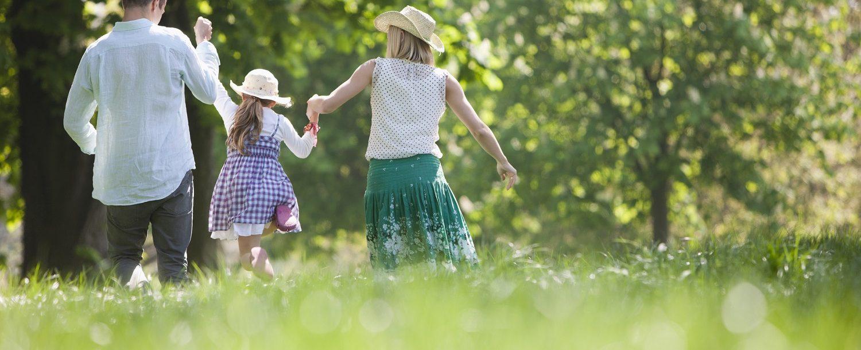 Family walking hand-in-hand through Cummings Park in Stamford, CT