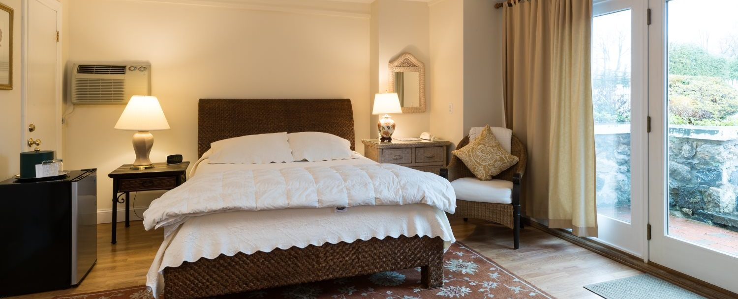 Queen size bed and private entrance of Room 2 at Stanton House Inn, a Greenwich, CT, bed and breakfast inn