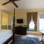 TV, queen size bed, porch, and sitting area of Room 28 at Stanton House Inn, a Greenwich, CT, bed and breakfast inn