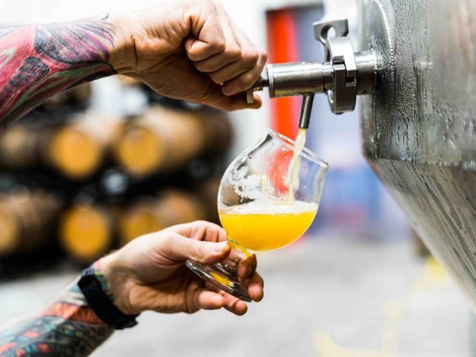man pouring beer from a tap at one of the best Connecticut breweries near Greenwich, CT