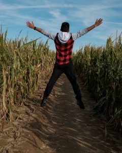 man jumping in the middle of a corn maze during fall in CT