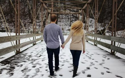couple walking through the snow on a bridge at one of the best places to visit in ct during winter vacation getaways