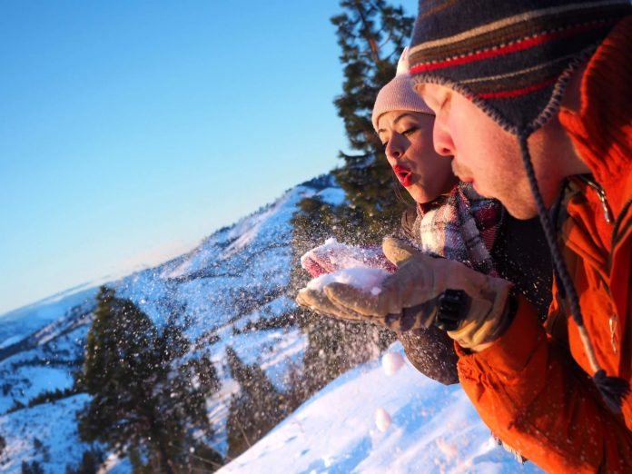 couple blowing snow while enjoying their winter vacation at one of the best places to visit in CT for winter getaways