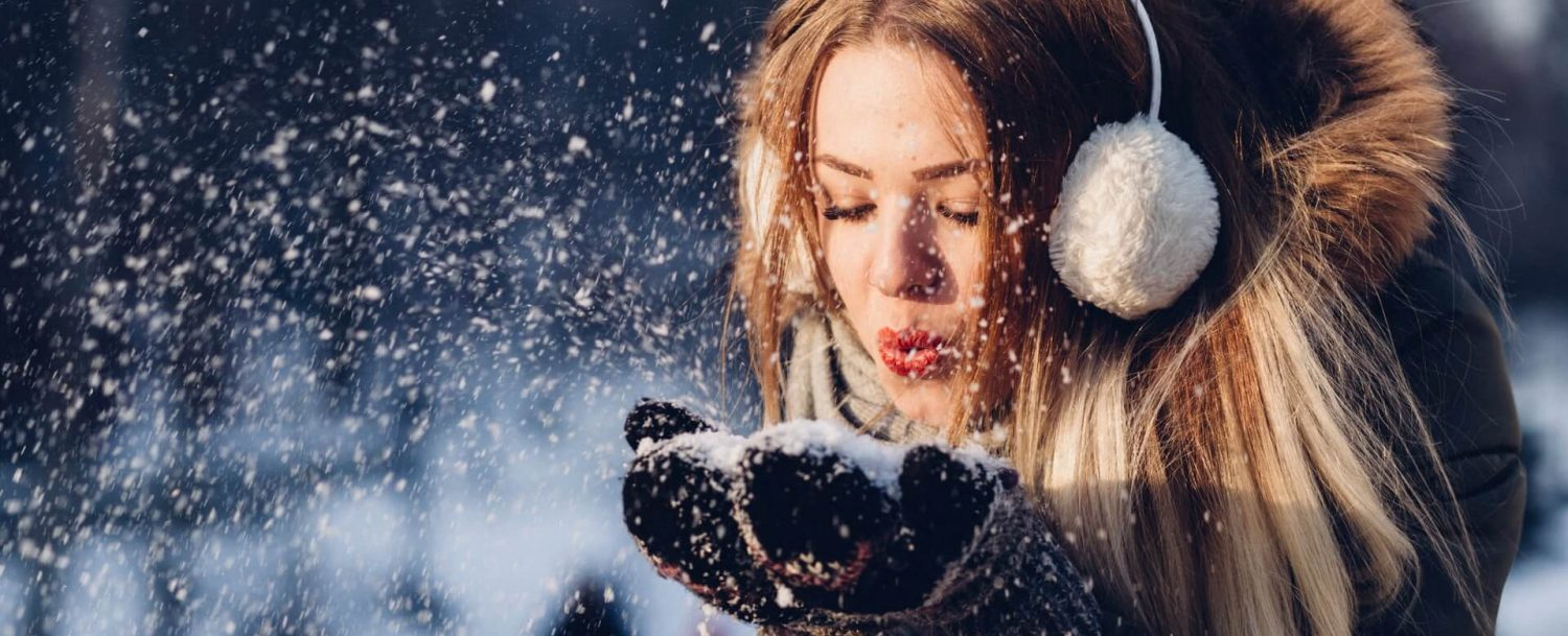 woman blowing snow while enjoying winter activities in ct