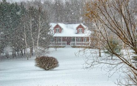 snow falling around a house