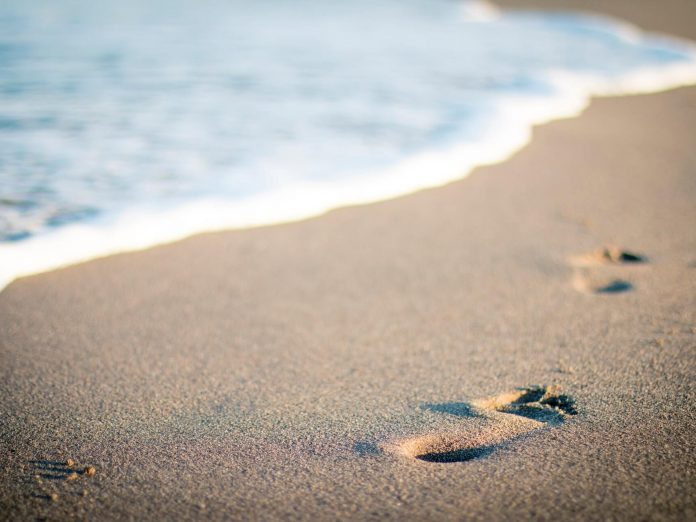 footsteps in the sand at one of the best Connecticut beaches
