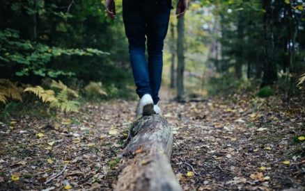 hiker walking along a log